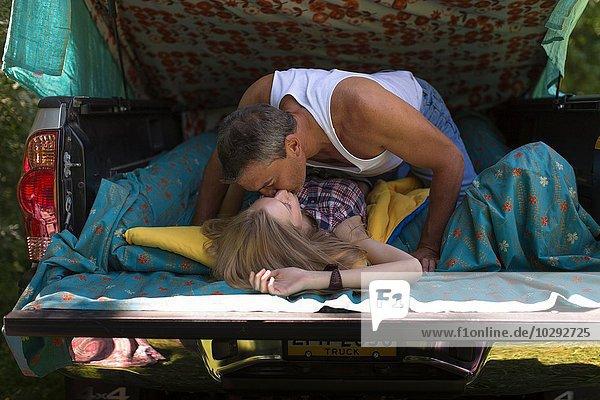 Reifer Mann und Freundin küssen sich im Stiefel  während sie campen.