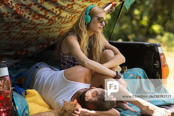 Junge Frau mit Kopfhörer und Freund im Stiefel beim Zelten