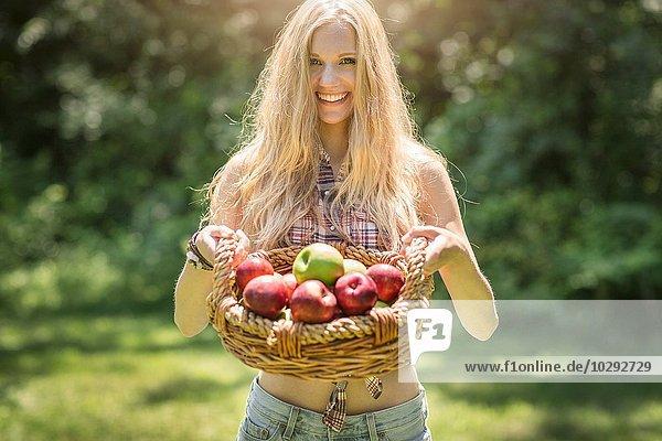 Porträt einer jungen Frau  die einen Korb mit frischen Äpfeln im Garten hält.