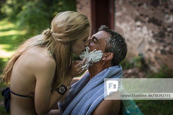 Junge Frau küsst Freund mit Rasiercreme am Kinn im Ferienhaus