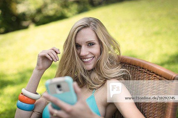 Portrait einer jungen Frau im Bikini-Top mit Smartphone im Garten