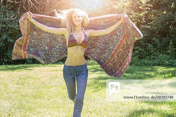 Porträt einer jungen Frau im Bikini-Top mit Schal im Garten