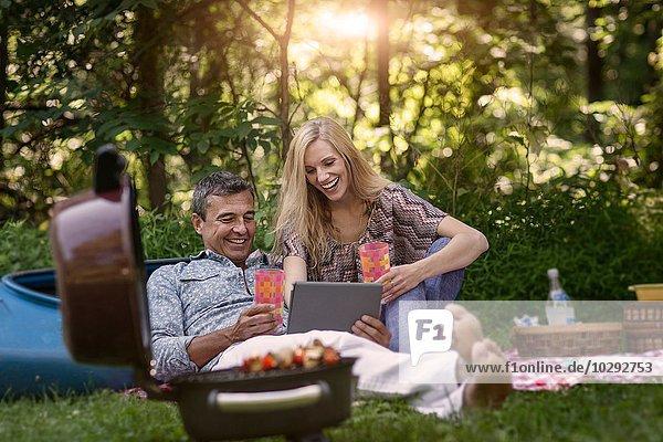 Erwachsener Mann und Freundin beim Picknickgrill auf dem digitalen Tablett