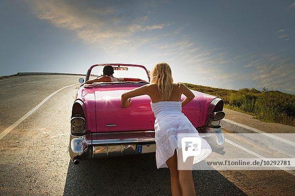 Frau schiebt Cabrio auf der Straße