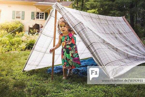 Porträt eines Mädchens  das aus einem selbstgebauten Gartenzelt schaut.