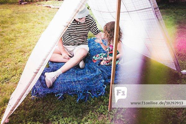 Mädchen und Großvater beim Spielen im hausgemachten Gartenzelt