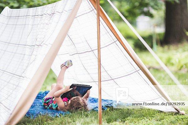 Mädchen auf dem Rücken liegend im hausgemachten Gartenzelt mit Blick auf digitales Tablett