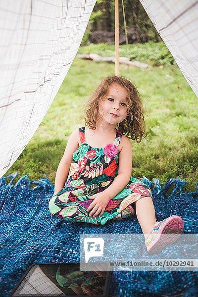 Porträt eines Mädchens im hausgemachten Gartenzelt mit digitalem Tablett
