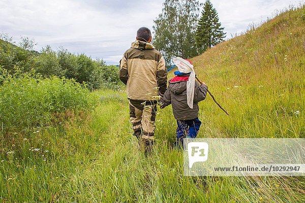 Vater und Sohn gehen durchs Feld  tragen Fischernetz  Rückansicht