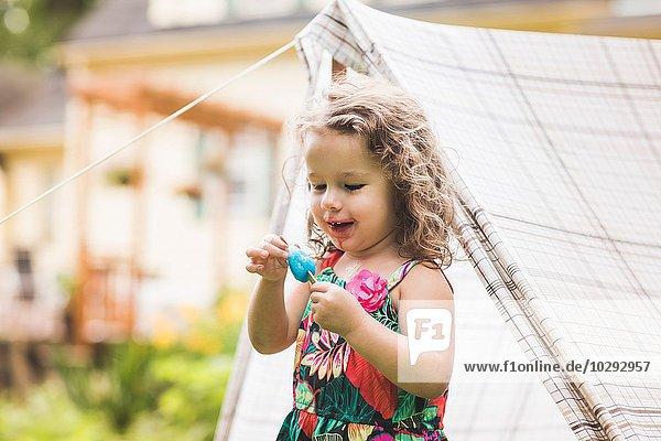 Mädchen berührt Eis am Stiel im Garten
