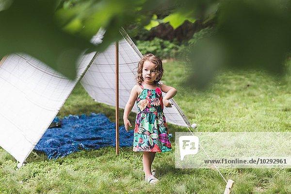 Abgelenktes Mädchen spielt mit Schnur auf hausgemachtem Gartenzelt