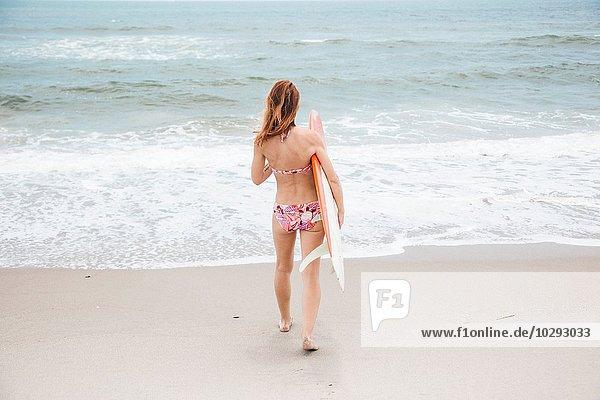 Mittlere erwachsene Frau auf dem Weg zum Meer  hält Surfbrett  Rückansicht