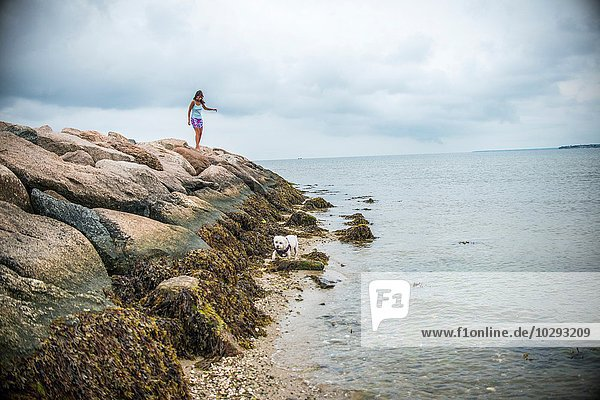 Reife Frau  die über Küstenfelsen tritt  Cape Cod  USA