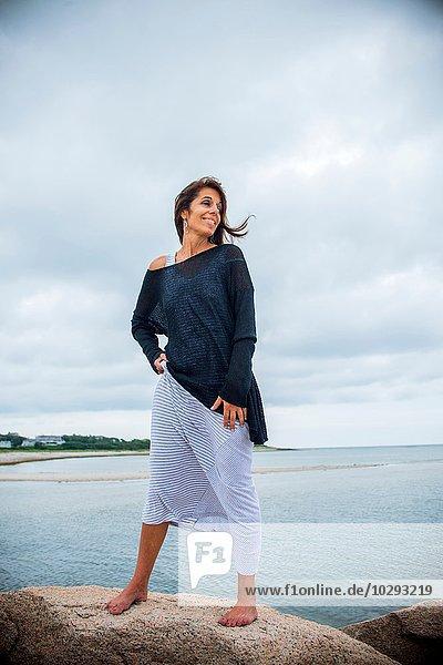 Reife Frau  die von den Felsen an der Küste über die Schulter schaut  Cape Cod  USA