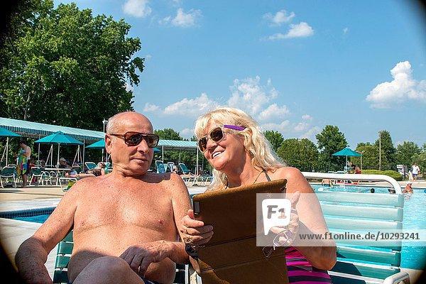 Seniorenpaar beim Betrachten des digitalen Tabletts im Freibad