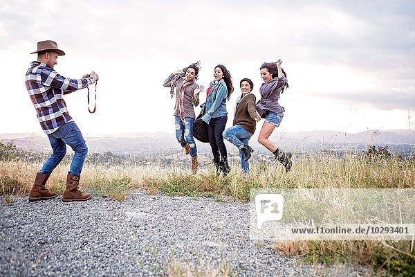 Junger Mann fotografiert seine vier erwachsenen Schwestern beim Sprung auf den Hügel
