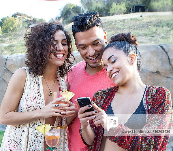 Young man and two sisters reading smartphone texts in garden