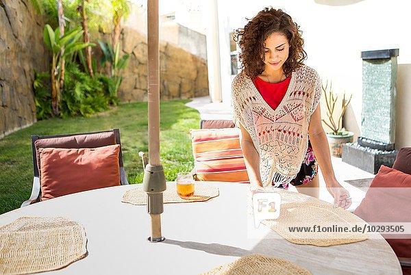 Junge Frau legt Tischsets auf Terrassentisch