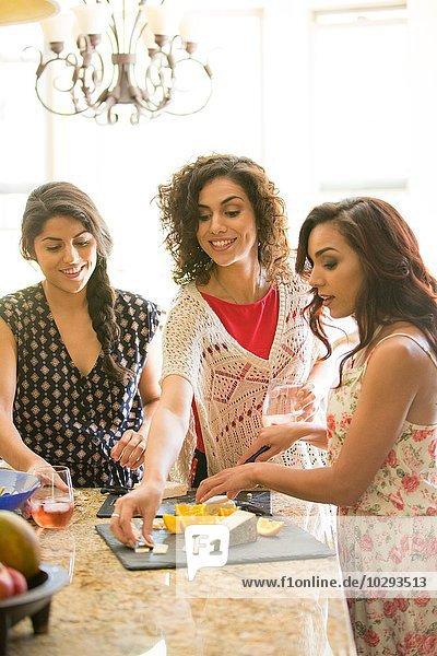 Drei erwachsene Schwestern beim Snacken vom Käsebrett