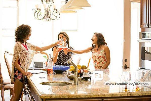 Drei erwachsene Schwestern  die einen Rosenwein-Toast in der Küche aufziehen.