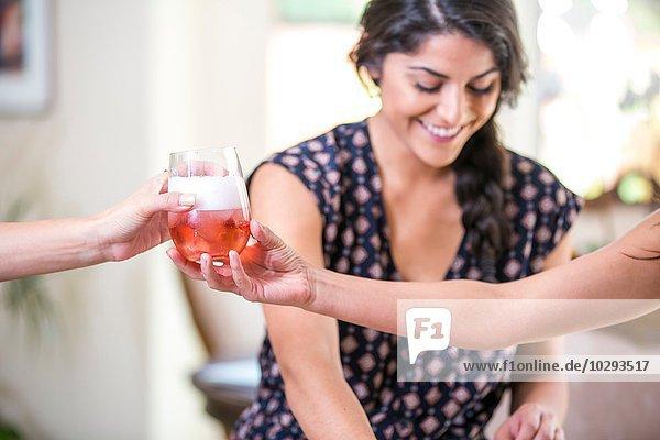 Erwachsene Schwestern in der Küche  die ein Glas Rosenwein reichen.