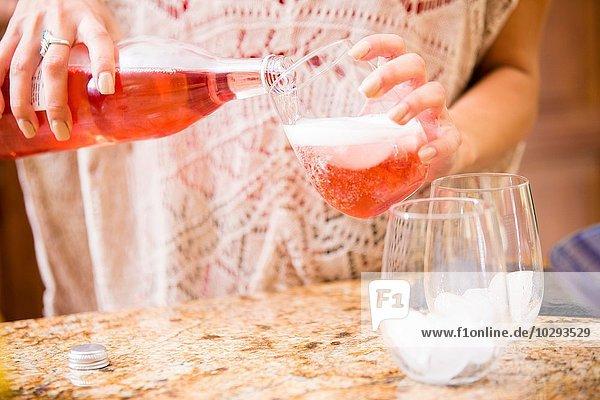 Nahaufnahme einer jungen Frau  die Rosenwein an der Küchentheke ausschenkt.