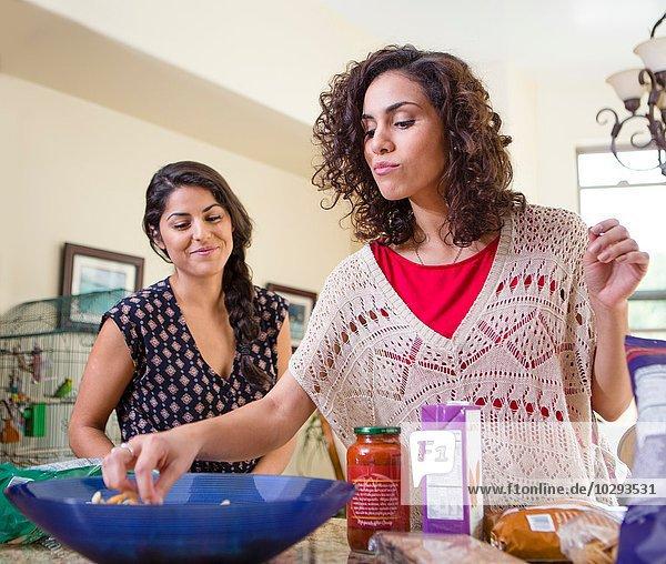 Zwei erwachsene Schwestern bei der Zubereitung von Essen und Snacks aus der Schüssel