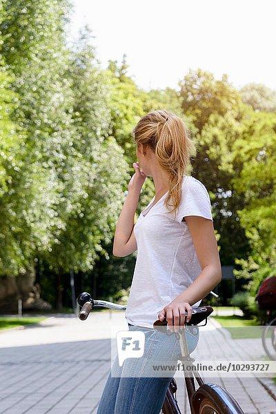 Junge Frau mit Pferdeschwanz  die sich gegen das Fahrrad lehnt und wegschaut.