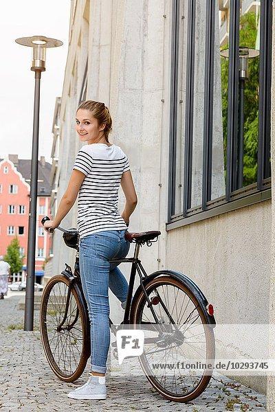 Junge Frau auf dem Fahrrad schaut über die Schulter und lächelt in die Kamera