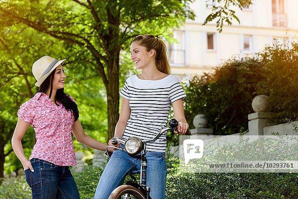 Junge Frau auf dem Fahrrad im Gespräch mit junger Frau mit Panamahut  von Angesicht zu Angesicht lächelnd