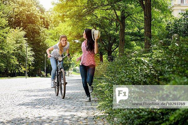 Vorderansicht einer jungen lächelnden Frau auf dem Fahrrad  die eine junge Frau mit Panamahut jagt.