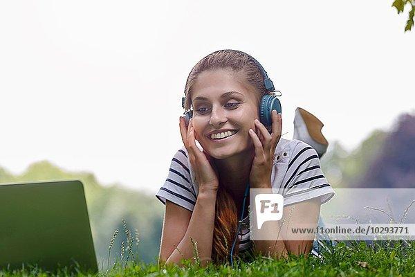 Junge Frau mit Kopfhörer auf Gras liegend  auf Ellbogen liegend  mit lächelndem Blick auf den Laptop.