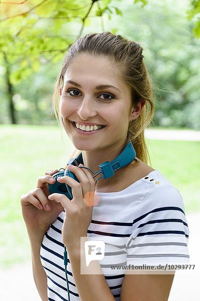 Portrait of young woman holding headphones looking at camera smiling