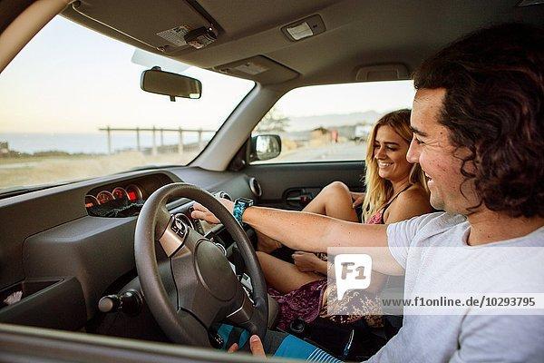 Paar im Auto auf der Reise  lächelnd