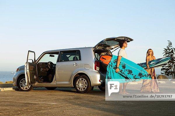 Paar  das Surfbretter aus dem Kofferraum des Autos nimmt