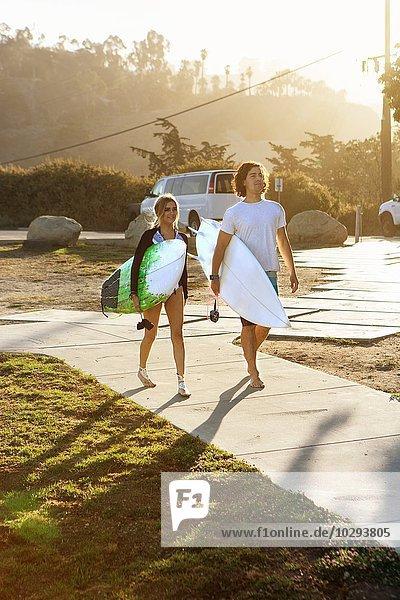 Paar  das Surfbretter trägt und zum Strand geht