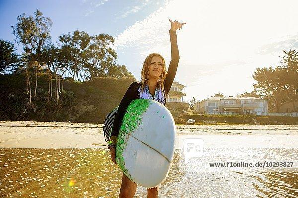 Junge Frau im Meer stehend  auf das Meer blickend  Surfbrett haltend  mit der Hand gestikulierend