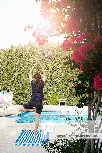Rear view of mature woman in yoga pose at poolside