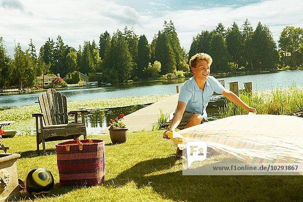 Mann legt Picknickdecke auf Gras  See im Hintergrund  Seattle  Washington  USA