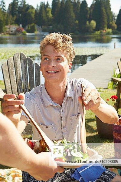 Mann  der sich selbst beim Salat auf der Lake Party bedient  Seattle  Washington  USA