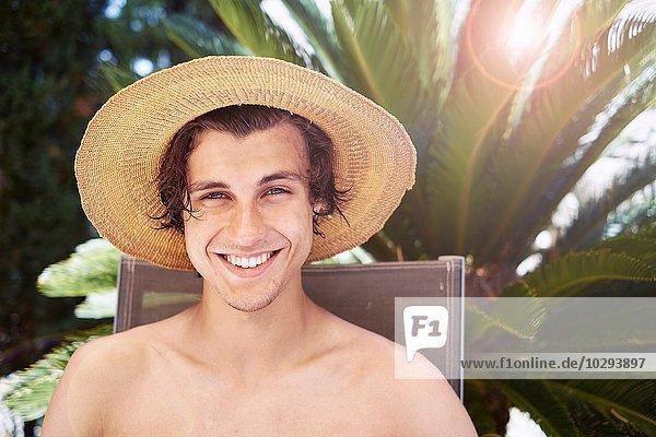 Porträt eines lächelnden jungen Mannes mit Sonnenhut