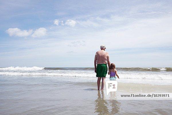 Rückansicht eines älteren Mannes  der mit seiner Enkelin im Meer paddelt.