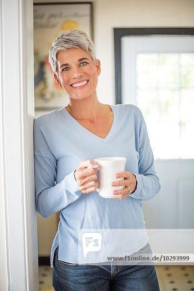 Porträt einer grauhaarigen reifen Frau mit blauen Augen  die in der Küche Kaffee trinkt.
