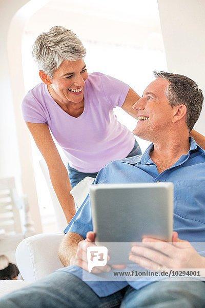 Reife Paare beim Chatten mit dem digitalen Tablett