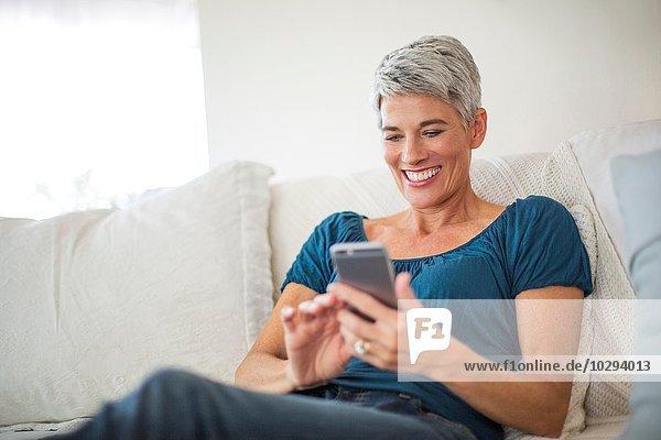 Fröhliche reife Frau  die auf dem Sofa liegt und auf dem Smartphone texten kann.