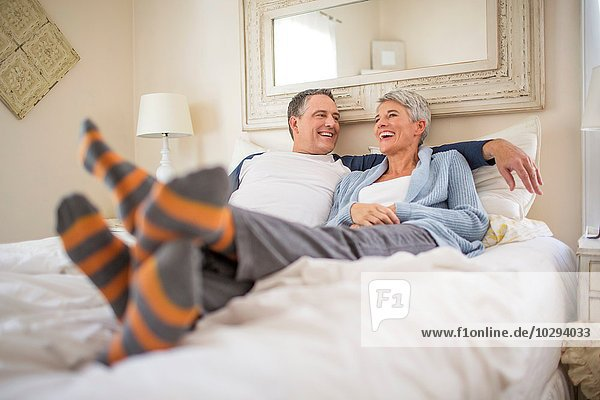 Reife Paare beim Plaudern und Entspannen im Bett