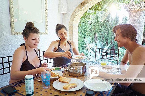 Reife Frau mit Sohn und Tochter beim Mittagessen auf der Terrasse der Ferienwohnung