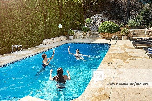 Reife Frau wirft Ball mit Sohn und Tochter im Schwimmbad