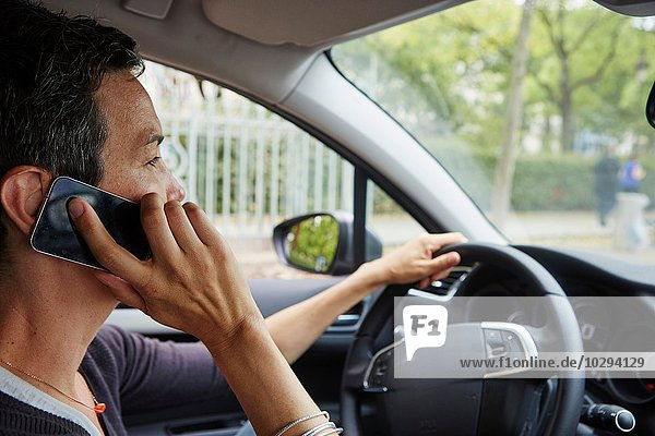Frau fährt Auto  mit Smartphone