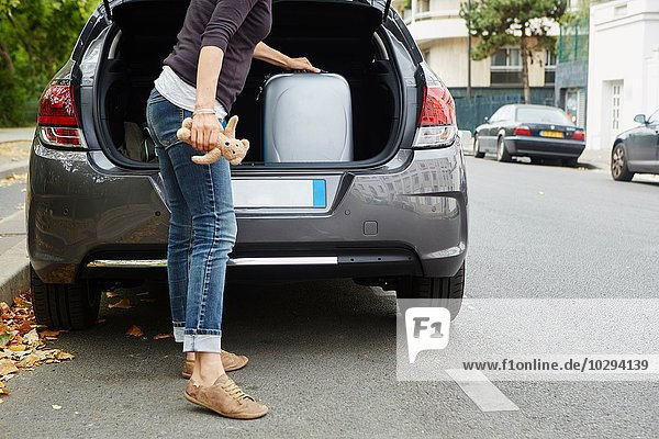 Woman standing beside car  putting suitcase in open boot